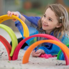 cute-elementary-girl-building-a-rainbow-structure-picture-id1158090081